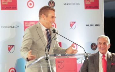ESPN soccer analyst and former U.S. national team player Taylor Twellman gets a smile out of Atlanta United owner Arthur Blank at the Oct. 23 news conference announcing that MLS is bringing its All-Star Game to Mercedes-Benz Stadium next year. (Photo by Itoro Umontuen)