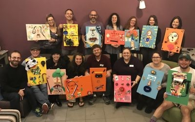 Participants in the JumpSpark Professional seminar in Israel show the self-portraits they made with found materials. Seated (from left) are artist Hanoch Piven; Ezra Flom, the director of youth and family programming at Temple Kol Emeth; Nicole Andronescu Flom, the assistant director of education at Ahavath Achim Synagogue; Bobbee Griff, the youth adviser at Temple Beth Tikvah; Adam Griff, the regional director of youth engagement for NFTY-SAR; Elizabeth C. Foster, a family and teen educator at The Temple; Molly Okun, the director of youth and teen engagement at Temple Sinai; and Jason Price, a program manager for the Atlanta Jewish Teen Initiative. Standing (from left) are Hope Chernak, the executive director of the Atlanta Jewish Teen Initiative; Rabbi Gabby Dagan of the Leo Baeck Education Center; Rich Walter, the associate director for Israel education at the Center for Israel Education; Hannah Zale, the music director for In the City Camp and a religious school music educator and youth adviser at Congregation B'nai Torah; Susan Cosden, the director of education at Temple Beth Tikvah; Jody Gansel, a program manager for the Experiential Jewish Education Network; and Mira Hirsch, an artistic associate for Theatrical Outfit Project Tolerance at The Temple.