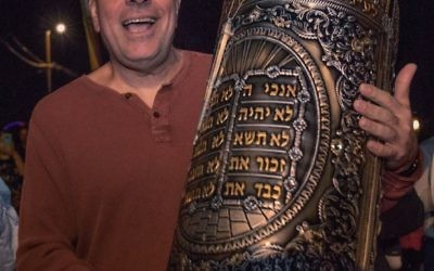 Alon's restaurant owner Alon Balshan helps carry the new Sephardic Torah during a procession along Chamblee-Dunwoody Road.