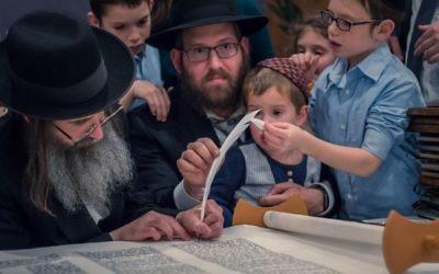 Rabbi Mendy Gurary helps write the last letter on the new Sephardic Torah dedicated in memory of Reuven Manoah.