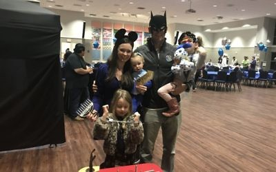 Parents Heather and Jeremiah Jarmin enjoy the camp expo while getting playful in costumes with children Ariella, 6, Zipporah, 4, and Davinah, 15 months.