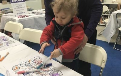 Scott Cohen and son Isaac, 16 months, get creative with markers at the booth for Marcus JCC day camps.