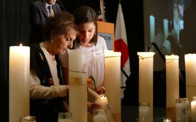 Holocaust survivor Janine Storch lights a memorial candle with the help of Emma Novitz.