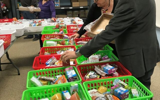 Rabbi Mark Zimmerman and others pack groceries for meal donations at Congregation Beth Shalom on Wednesday, Feb. 7.