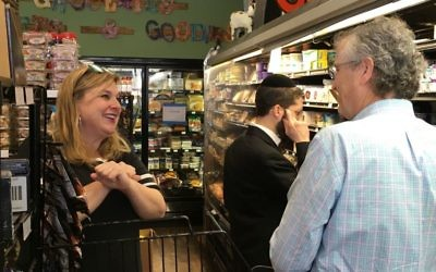 The Spicy Peach co-owner Jodi Wittenberg helps a customer on a crowded Sunday before Passover. (Photo by Leah R. Harrison)