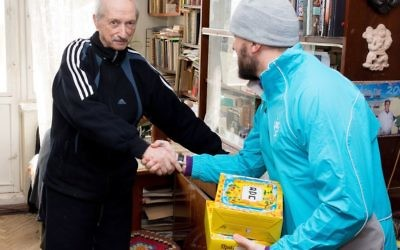 Photo courtesy JDC A JDC Jewish community youth volunteer delivers matzah to a needy Jewish senior before Passover in Kishinev, Moldova.