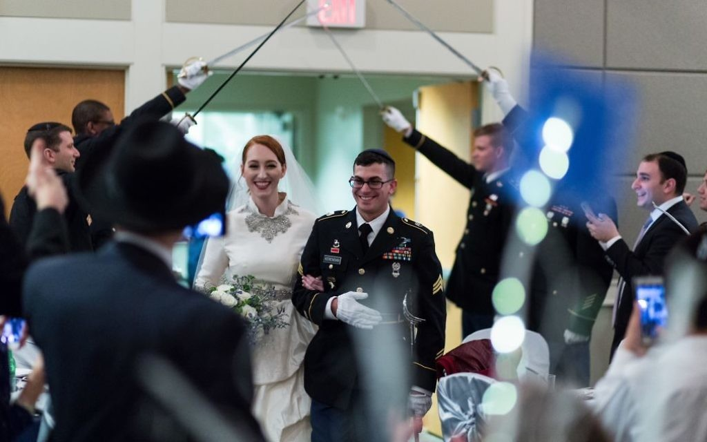 Keeping with military tradition, Ashley and Natan walk through an arch of sabers on their wedding day in Congregation Beth Jacob's Heritage Hall.