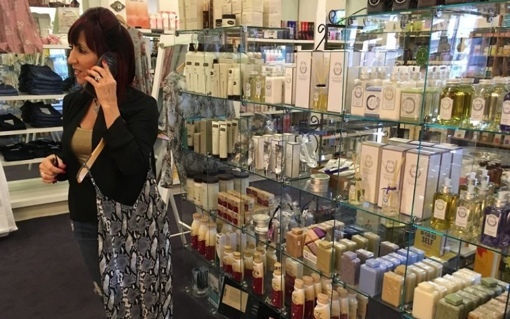 Veronica's Attic co-owner Cecily Ross multitasks in front of the well-stocked bath and body display.