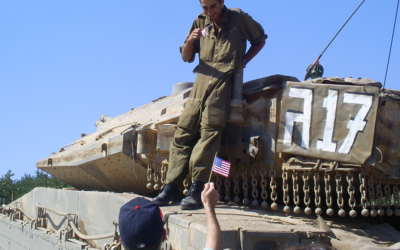 Scott Allen, wearing an Atlanta Braves hat, gives an American flag to an Israeli soldier during the Second Lebanon War in 2006.