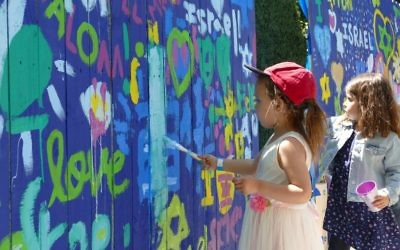 Young artists decorate a fence with messages of love for Israel.
