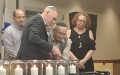 Ken Winkler helps Holocaust survivor Bernie Gross light the last candle as Margie Gelernter looks on. (Photo by Sarah Moosazadeh)