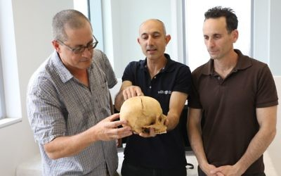 (From left) Boaz Zissu, Yossi Nagar and Haim Cohen examine the skull of what is believed to be a victim of blood vengeance. (Israel Antiquities Authority photo)
