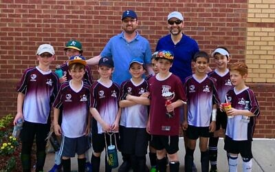 Fresh off finishing second in their league tournament are under-10 JCC soccer players (from left) Asher Frank, Malachi Freedman, Noam Glazer, Ari Fleshel, Aryeh Rabin, Akiva Senior, Shalom Yosef Fleshel, Paul Budhram, Zev Rodbell and Gavin Rolnick, backed by coaches Rabbi Yaakov Fleshel and Tal Frank.