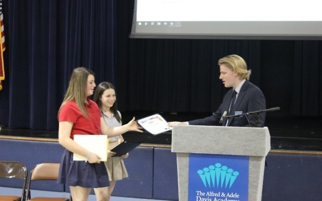 Jessie Schulhoff (left) and Ava Stark receive the StudentCam honorable mention from C-SPAN representative Joel Bacon. (Photo courtesy of the Davis Academy)