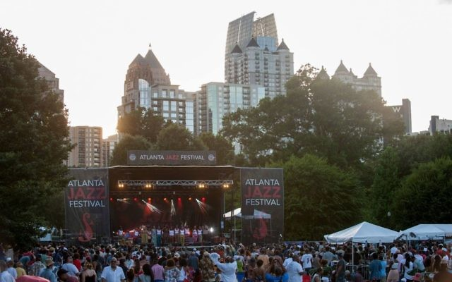 Midtown skyscrapers provide a scenic background for the Atlanta Jazz Festival at Piedmont Park.
