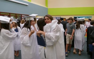 Ava Stark and Jessie Schulhof share a goodbye hug before they leave for high school.