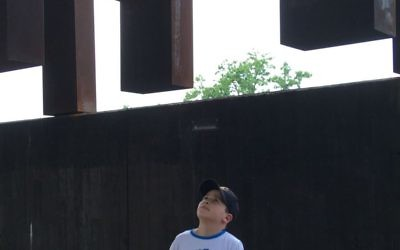 Marita Anderson's son takes in the spectacle of the National Memorial for Peace and Justice.