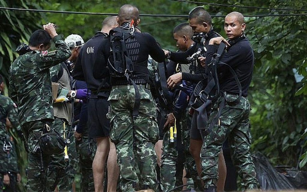 Rescuers prepare dive gear at the entrance to a cave complex in which 12 boys and their soccer coach are trapped in Mae Sai, Chiang Rai province, in northern Thailand, July 4, 2018.
