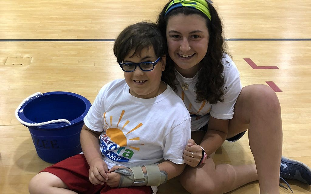 Counselor Jenna Grossman, a Davis Academy graduate, works with children with cancer, such as the one pictured, along with their siblings.