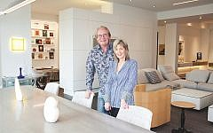 Cb and Hillary Miles pose by the porcelain, steel and aluminum table by MDF Italia with marble figures by Hillary's late aunt Sylvia Gould. The background (left) shows guestroom bookshelves designed by Cb and (right) the expansive living room. The maple art deco barrel chair is by Brueton.