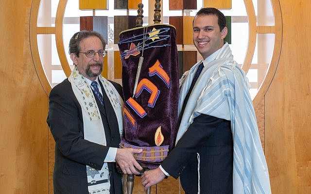 Emeritus Rabbi Harvey Winokur (left) passes a Czech Torah scroll that survived the Holocaust to Rabbi Jason Holtz.