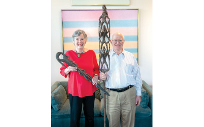 Ray Ann Kremer and George Shapiro hold primitive wood artifacts in front of paintings by Ida Kohlmeyer (Tulane/Newcomb professor) and Burton Callicott (Cloud Bands, 1974), a former professor at the Memphis Academy of Art. //Photos by Duane Stork