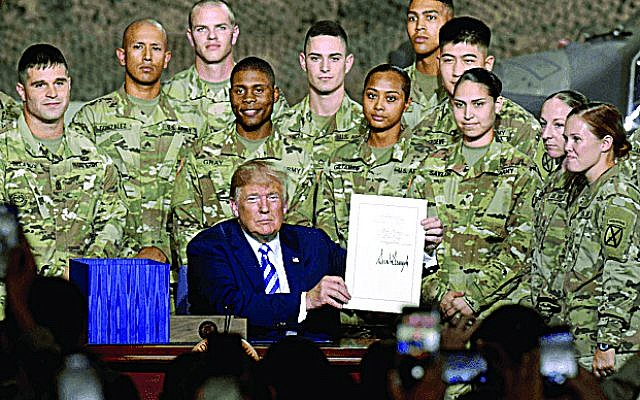 US President Donald Trump holds the John S. McCain National Defense Authorization Act for FY 2019.