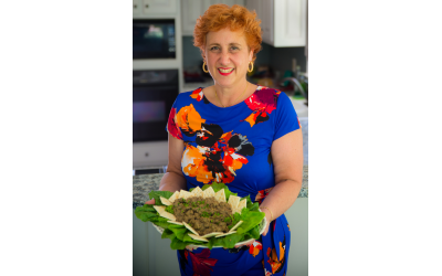 Phot by Robert Hainer// Terri Hitzig proudly holds a tray of her Hungarian grandmother Elsie's chopped liver, garnished with leafy greens and served with saltines.