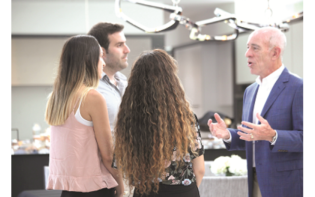 Stan Sunshine, a major program donor, speaks with students as they visit his sukkah.