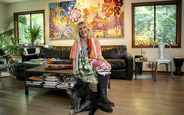 "Photos by Duane Stork // Karin Mervis poses with Schnauzer mix, Tanzi, in front of her colorful ""Babylon 2"" and ""Babylon 3."""