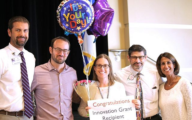 Epstein Head of Schoolwide Programs and Digital Learning and Technology Aaron Griffin, Elementary Principal David Welsher, Head of School David Abusch-Magder and Preschool Principal Stephanie Wachtel (right) present the teacher innovation award to Music Specialist Gale Berman (center).