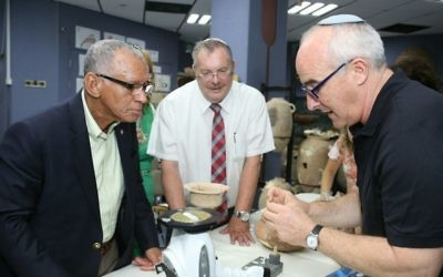 Aren Maeir (right), the director of the Ackerman Family Bar-Ilan University Expedition to Gath, shows one of the finds to NASA Administrator Charlie Bolden (left) and university President Rabbi Daniel Hershkowitz in this file photo from 2015. (Photo by Yoni Reif)
