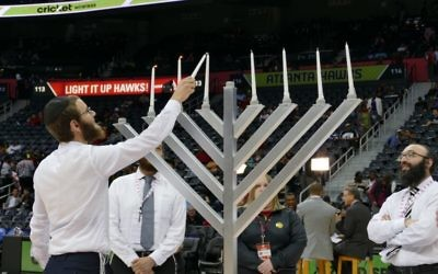 Menachem Loebenstein lights the menorah while Rabbi Isser New looks on.