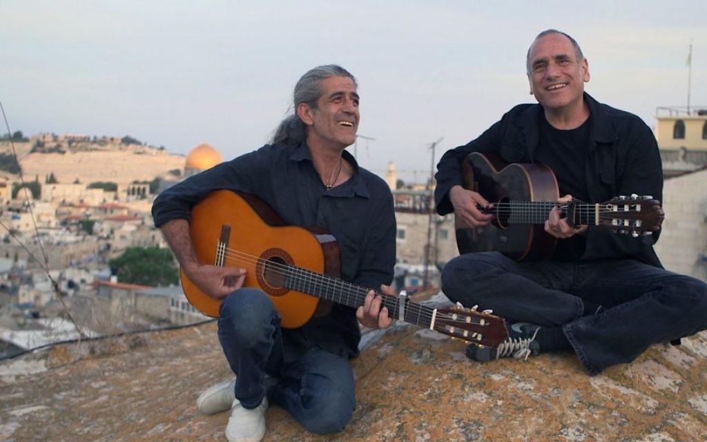 "David Broza sits on Palestinian filmmaker Issa Freij's rooftop in the Muslim Quarter of Jerusalem in a scene from ""East Jerusalem West Jerusalem."""