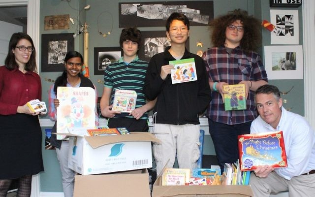 Teachers Mary Catherine Stoumbos and Edward Ellis flank Ben Franklin students (from left) Sophie Morris, Alex Warren, Ben Chen and Declan Greenwald with the donated books.