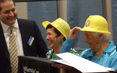 Frances Bunzl (right) and daughter Suzy Bunzl Wilner try on their ceremonial hard hats at the JF&CS annual meeting with agency CEO Rick Aranson.
