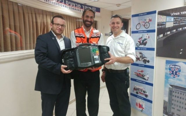 Former Atlantan Arie Pelta (center) on Aug. 28 receives the advanced defibrillator Atlanta donors paid for.