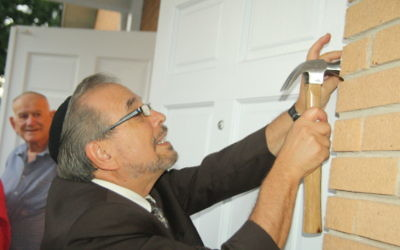 Rabbi Mark Kunis attaches a mezuzah to the new entrance of Shaarei Shamayim.