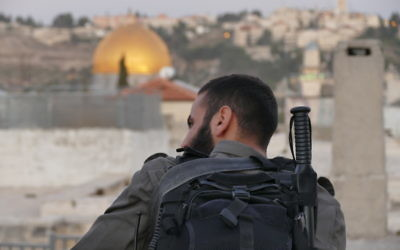 A soldier overlooks the dome of the rock in the old city of Jerusalem.