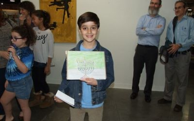 Ari Gordon collects his $50 Binders gift card as the winner of the 2016 AJT Chanukah Art Contest.