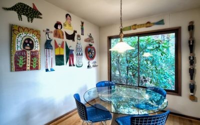 Folk art by Finster, Burnside, Miller and Brown creates a contrast with the midcentury furniture by Platner and Bertoia inside Carol and Paul Muldawer's woodsy Buckhead home. All photos by Duane Stork.
