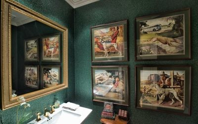 The guest bathroom displays a set of four vintage posters from the Greyhound Bus Co. and wallpaper made of roofing material. (All Photos by Duane Stork).