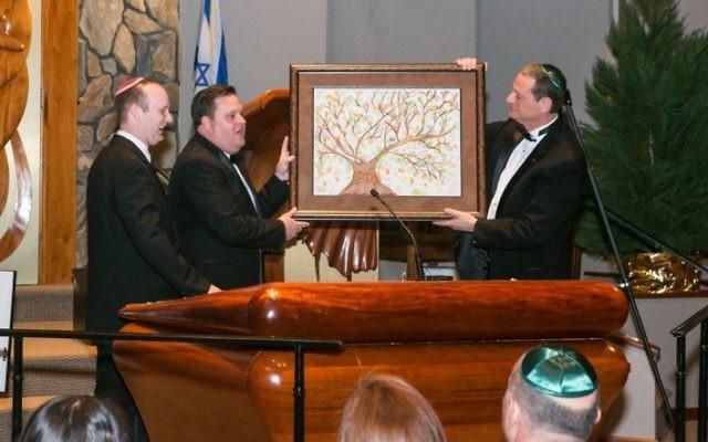 Etz Chaim President Todd Surden and past President Scott Rittenberg president the congregation's gift of a Tree of Life painting to Rabbi Daniel Dorsch.