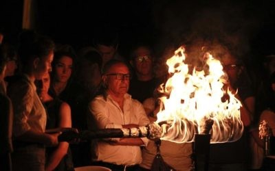 An Israeli lights one of the 12 torches for Independence Day on Mount Herzl