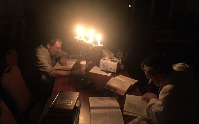 Barry Yaffe (left) and Rabbi Mendle Dickstein study Torah in the dark during the blackout at Congregation Beth Jacob at 6 a.m. March 22.