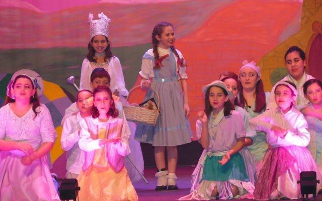 Dorothy (Shiraz Agichtein) meets Glinda (Eva Beresin) amid the Munchkins.