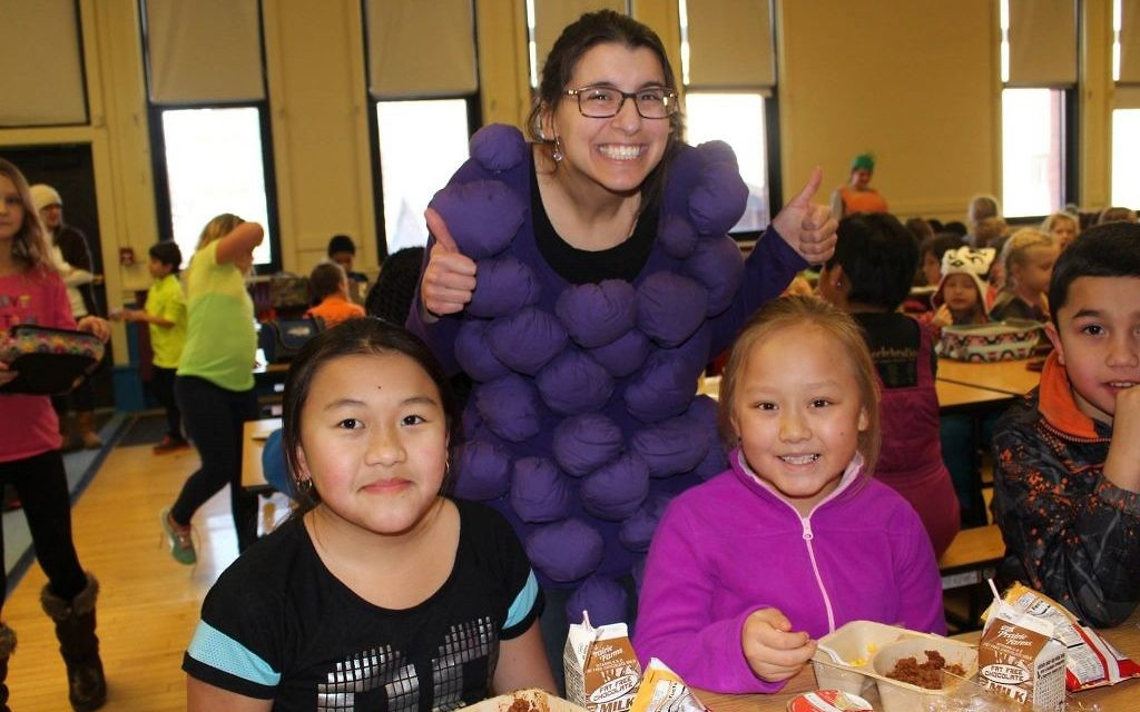 Emily Blustein doesn't usually wear the stereotypical farmer overalls during classroom lessons, although they are practical when she's outside. Instead, she often finds herself in costume while teaching about food and the environment.