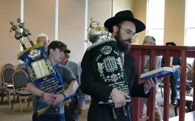 """Rabbi Ephraim Silverman leads a procession while blessing the new """"kindness Torah."""""""