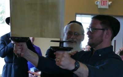 The hagba lifts and displays the newly completed Torah at Chabad of Cobb