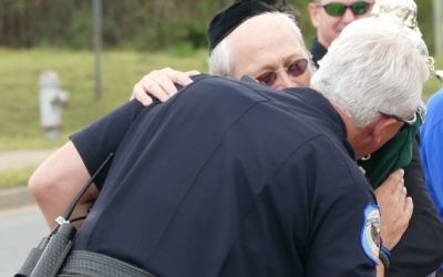 One of the Cobb County police protecting the parade kisses the new Torah at the urging of Rabbi Moshe Klein.